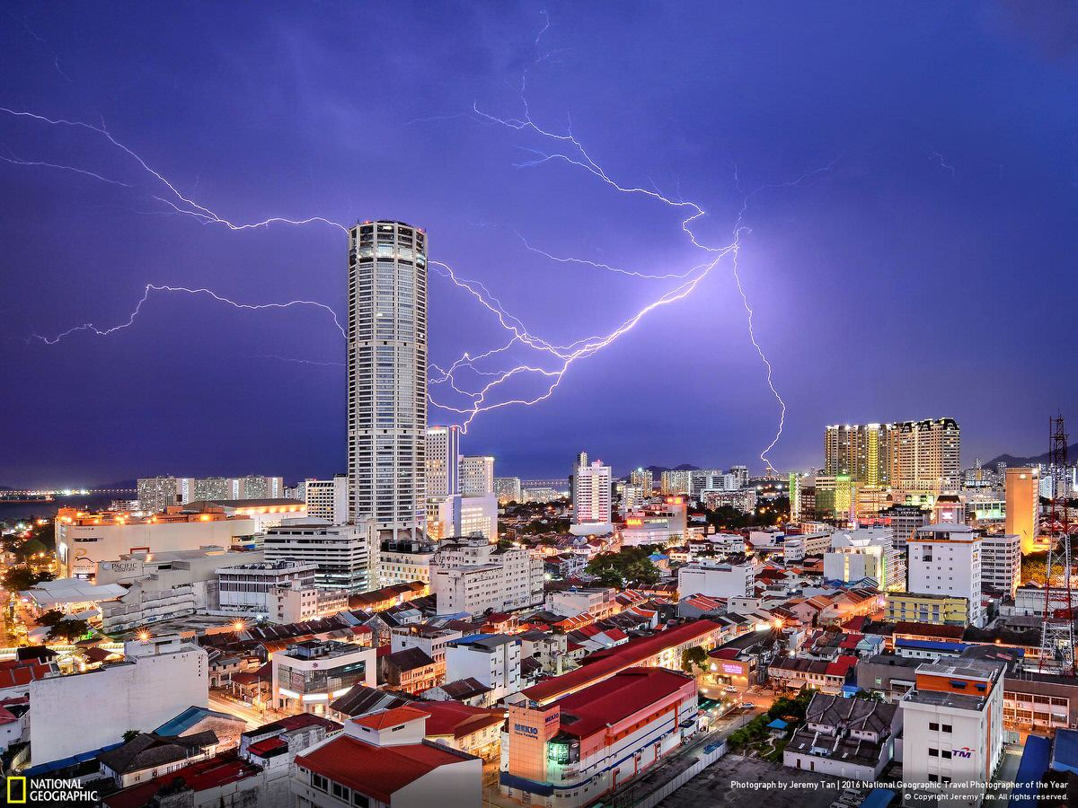 Lightning seemingly strikes Komtar Tower, the most iconic landmark of George Town, capital of Penang state in Malaysia, during a thunderstorm. It is symbolic of the rejuvenation that the city, famous for a unique blend of centuries-old buildings and modern structures, has enjoyed in recent years. While many of its old neighborhoods fell into neglect in the 1990s and early 2000s, a UNESCO World Heritage listing in 2008 sparked a transformation. | CATEGORY: Cities